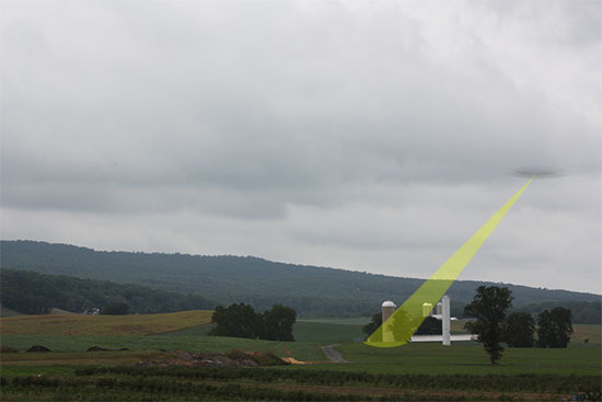 UFO with tractor beam on farm silo