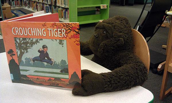 Stuffed gorilla reads Crouching Tiger book