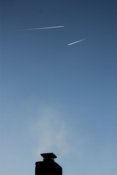 3 Smokes: 2 trails of planes in the sky and 1 chimney with smoke