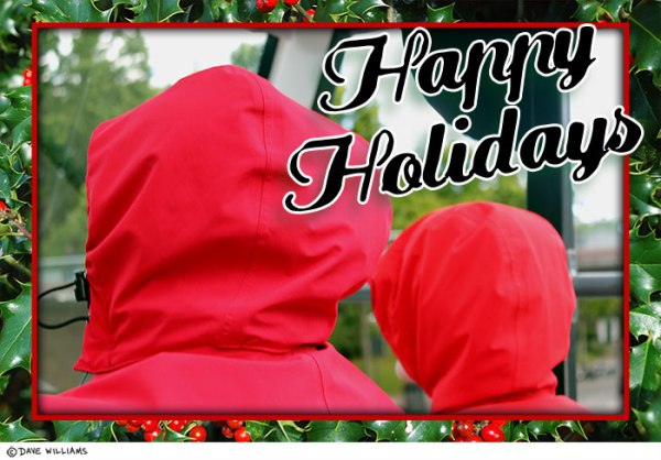 Possible Xmas card with two people with rain hoods on looking away from the camera