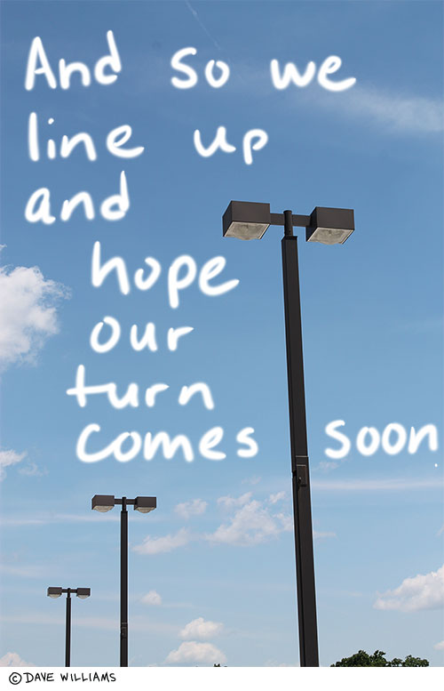 A photo of a line of streetlights, with the handwritten caption: And so we line up and hope our turn comes soon