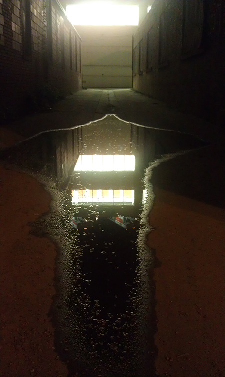 photo of an alley in Washington, DC where a puddle reflects light